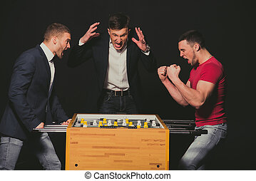 Boys play table football. The emotions of winning and losing.
