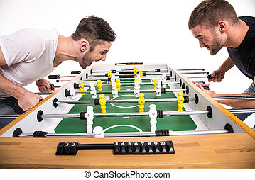 Boys play table football. The emotions of winning and losing. White background.