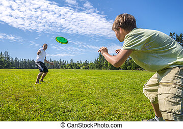 Boys playing a frisbee