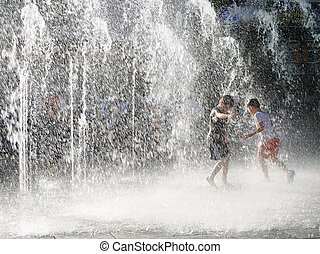 Boys playing in sprinkling water in summer time