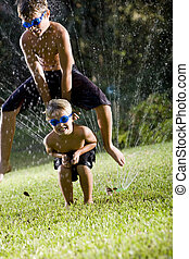 Boys playing leapfrog over lawn sprinkler - Children having...