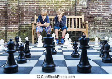 Boys playing outdoor chess - Two boys, sitting on a wooden...