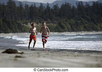 boys running at a beach - two young bouys running at a beach