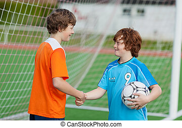 Boys Shaking Hands Against Net On Soccer Field - Little boys...