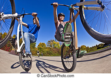boys show double wheely with the bike