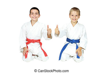 Boys sit in a ritual pose karate - Boys athletes sit in a...