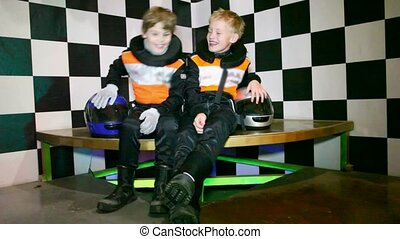 Boys sit in uniform for go-cart racing and wait the beginning of races