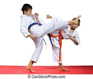 Boys sportsmen are training kicks