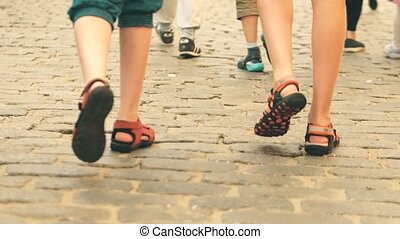 Boys wearing shorts and sandals walk on cobblestone pavement