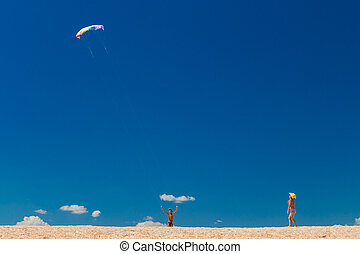Boys with colorful kite against blue sky at the beach