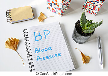 BP Blood Pressure written in notebook on white table