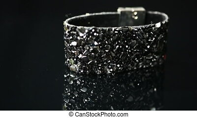 bracelet with many stones on reflective background