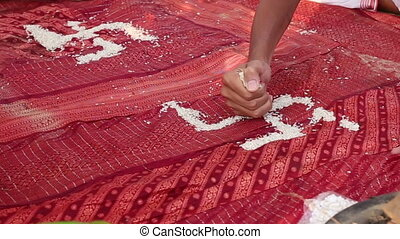 brahmin conducting Indian wedding ceremony making swastika with rice