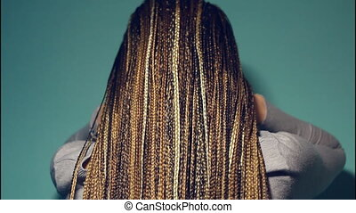 Braided African braids, she touches her braids