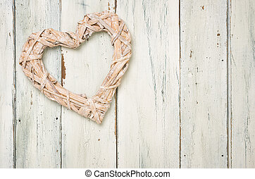 Braided heart on a white wooden background
