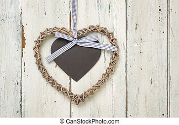 Braided heart with a sign on a white wooden background