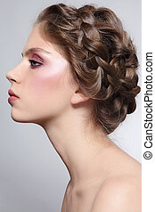 Profile portrait of young beautiful girl with braids hairdo