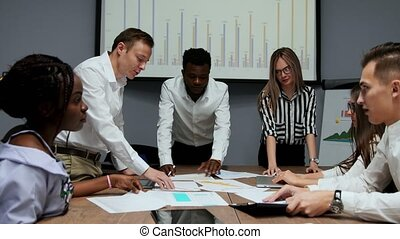 Brainstorm about creating your own cryptocurrency project. A group of people in the office are discussing economic sanctions. Creative ideas for business development. Multi-ethnic team in the office on the background of the chart on the projector discusses the effectiveness of the shares