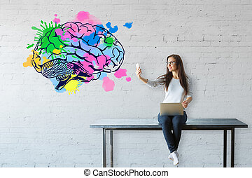 Brainstorm concept - Young woman sitting on table, using...