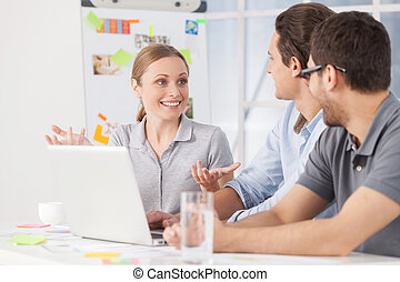 Brainstorming. Three young colleagues sitting together at their working place while woman telling something and gesturing