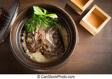 Braised fish head with rice in pot on the table