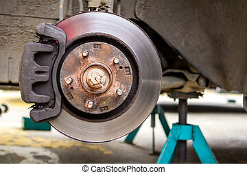 brake discs on the machine with the removed wheels on the jacks. wheel replacements