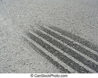 braking marks of a car tire on a grey asphalt road
