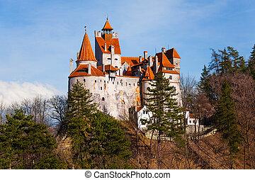 Bran Castle (Dracula castle) among trees on hill in Transylvania and Wallachia, Romania