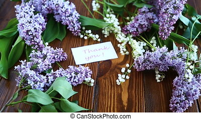 branch of blossoming spring lilac on a wooden table