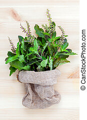 Branch of fresh red holy basil and holy basil flower from the garden in hemp sack bag on wooden background.