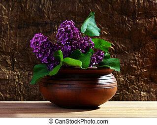 Branch of lilac in a ceramic vase.