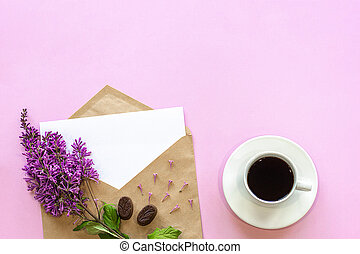 Branch of lilac on craft envelope with empty card and coffee