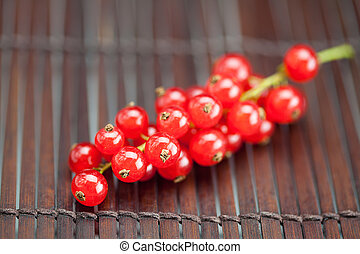 branch of red currants on a bamboo mat