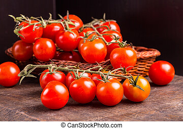 Branch of red tomatoes lying in a basket on a dark table.