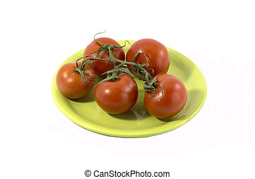 branch of red tomatoes on a round lime plate