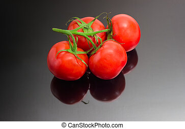 Branch of the red tomatoes on a dark reflective surface