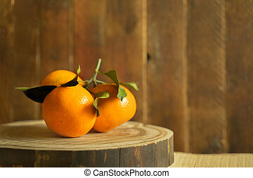 Branch of three mandarins is lying on wooden cut on wooden...