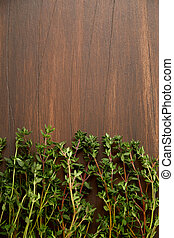 Branch of thyme on a dark wooden board. Free place for the...