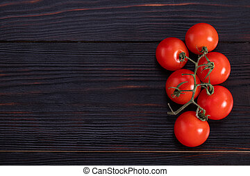 branch of tomato on a wooden background. Top view with copy space