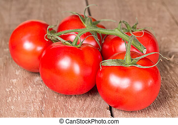 Branch  tomatoes on a wooden surface