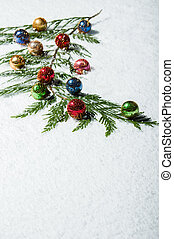 Branch with Christmas ornaments in snow