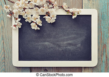 Beautiful blossom branch with framed blackboard over wooden background