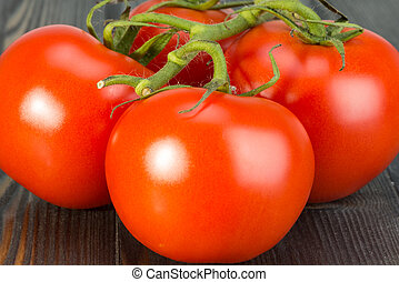 branch with ripe tomatoes on a wooden surface