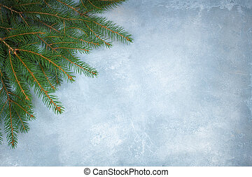 Branches of a Christmas tree on the blue concrete background