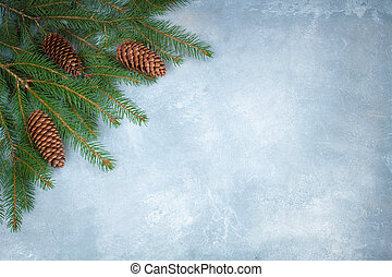 Branches of a Christmas tree with cones on the blue concrete background