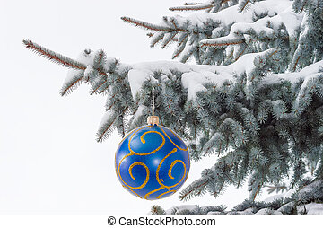 Branches of blue spruce covered with snow with Christmas ornament