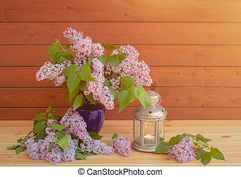 Branches of lilac in blue vase and lantern near on wooden table. Selective focus.