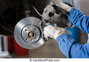 Brand new brake disc on car in a garage. Auto mechanic repairing  .