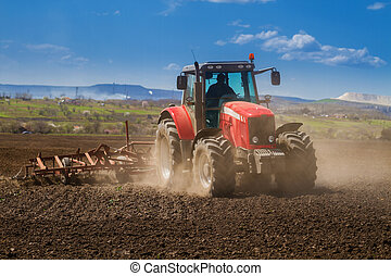 Brand new red tractor on the field working