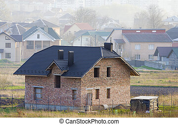 Brand new spacious brick two story residential house with tiling roof and windows openings in suburban neighborhood on background of distant city. Building, mortgage and rel estate property.